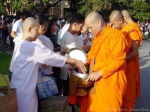 A Buddhist nun gives alms to a monk